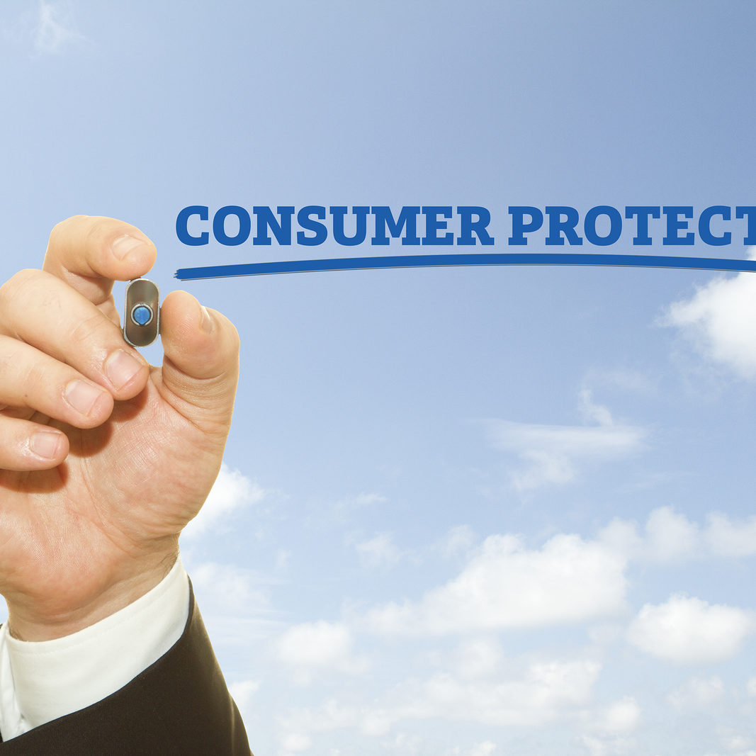 """Businessman Hand writing """"Consumer Protection"""" words ."""